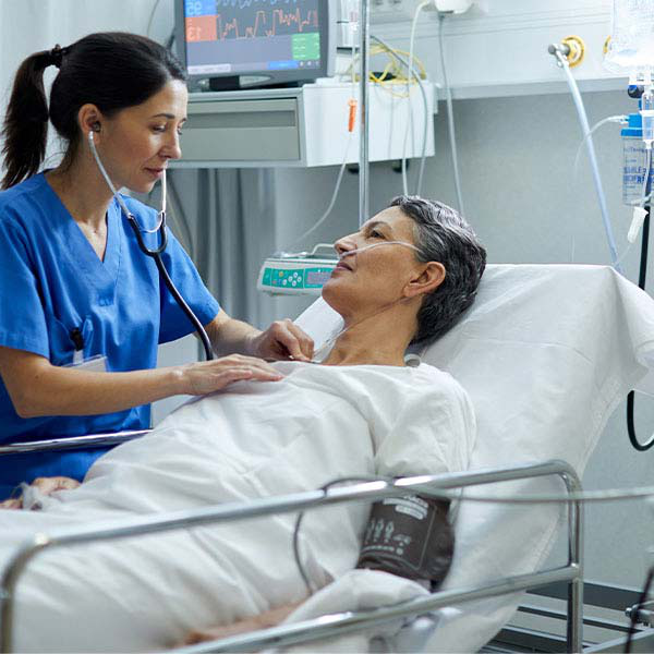 A nurse standing next to a patient in a hospital bed.